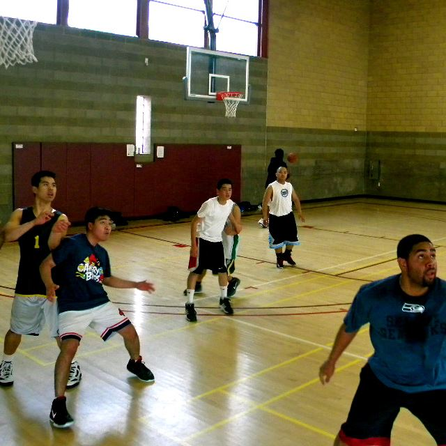 Young men playing basketball in an indoor gym 1