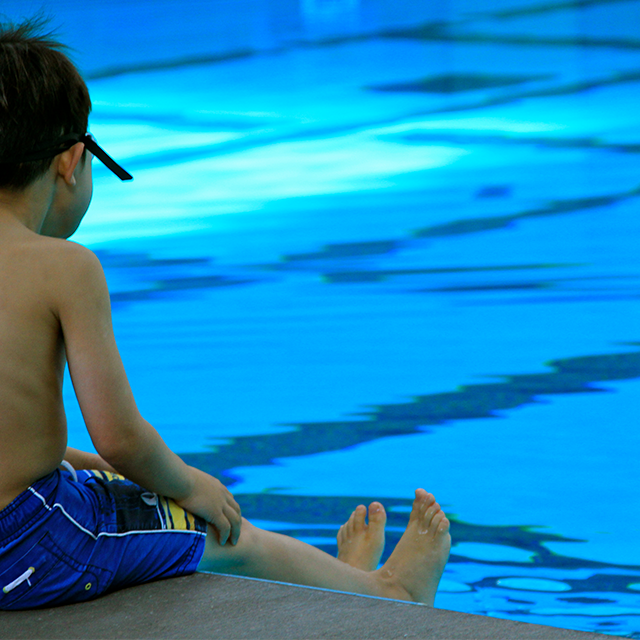 Little boy sitting at the edge of the pool