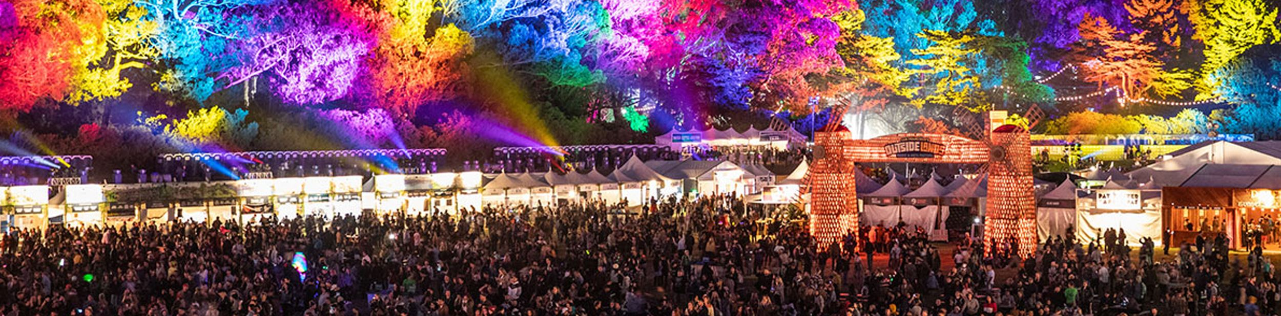 Crowded festival with colorful lights projected on the trees
