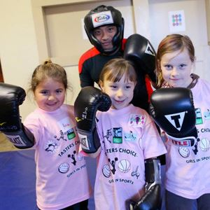 Girls and boxing instructor wearing boxing gloves
