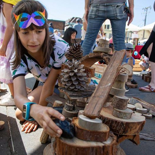 Kids building with pieces of wood, sticks, and pine cones