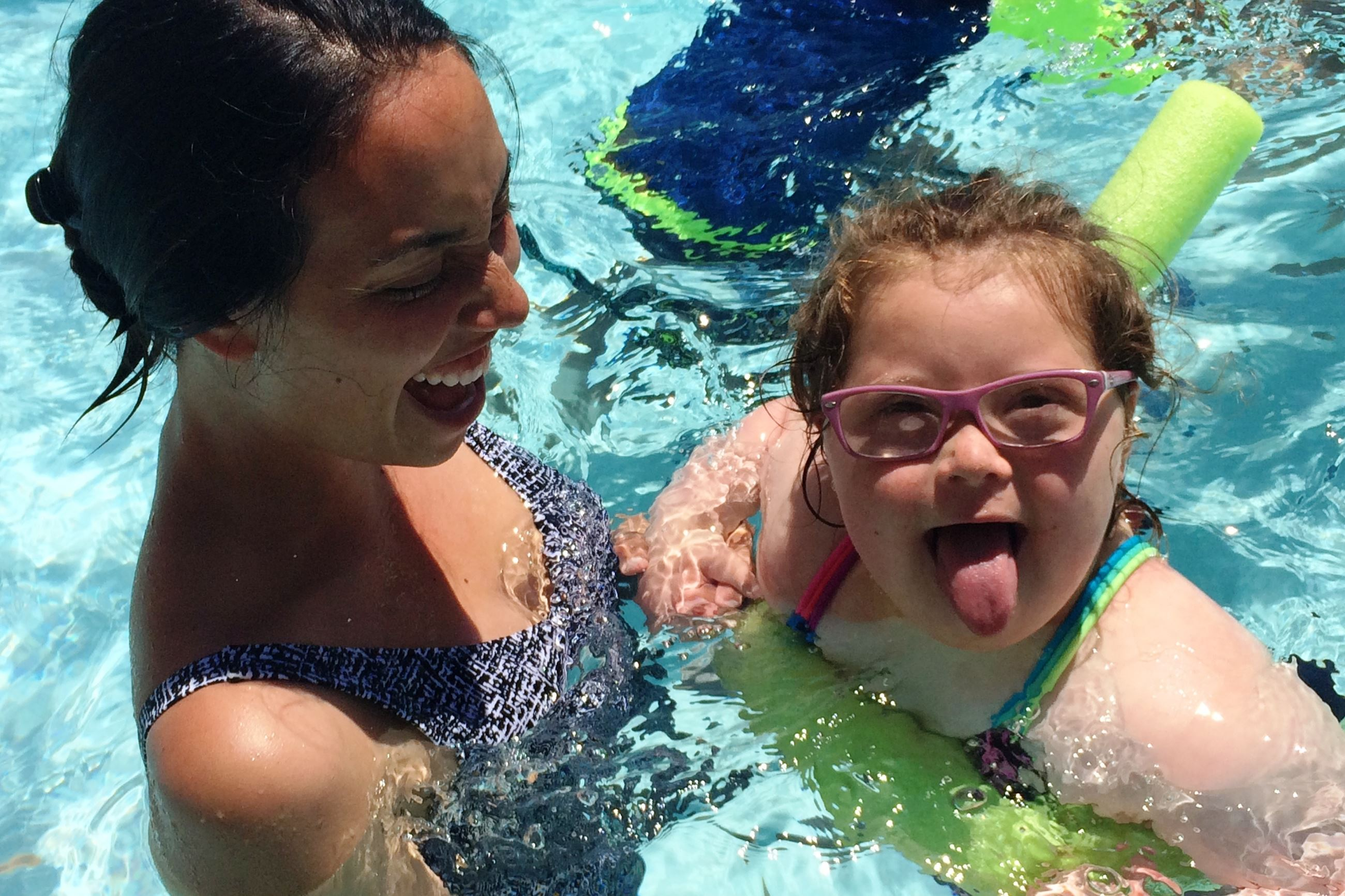 girl in pool smiling with staff person supporting her