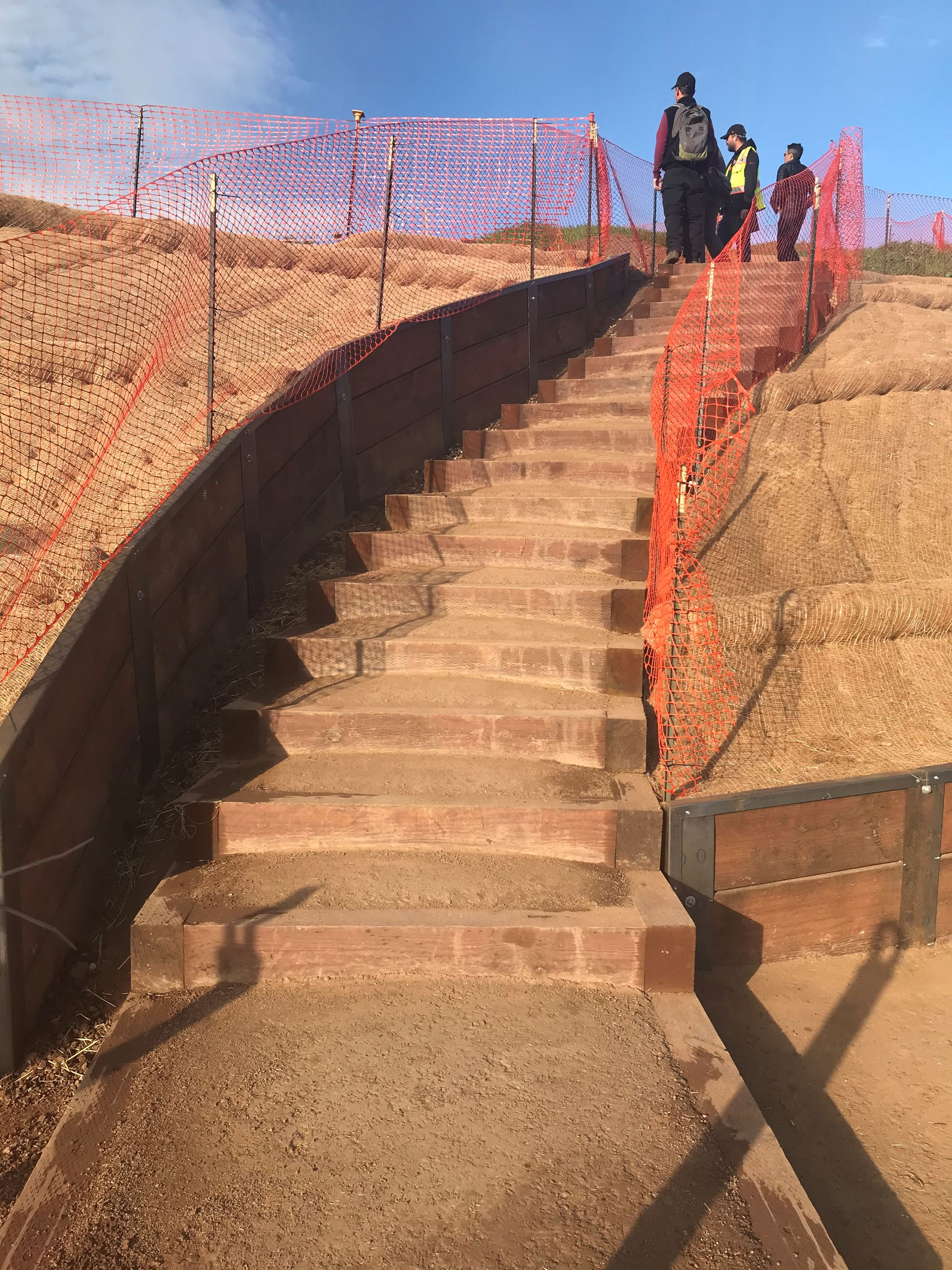 View of Box Steps Up Bernal Hill with orange construction fencing and crew standing at the top of th
