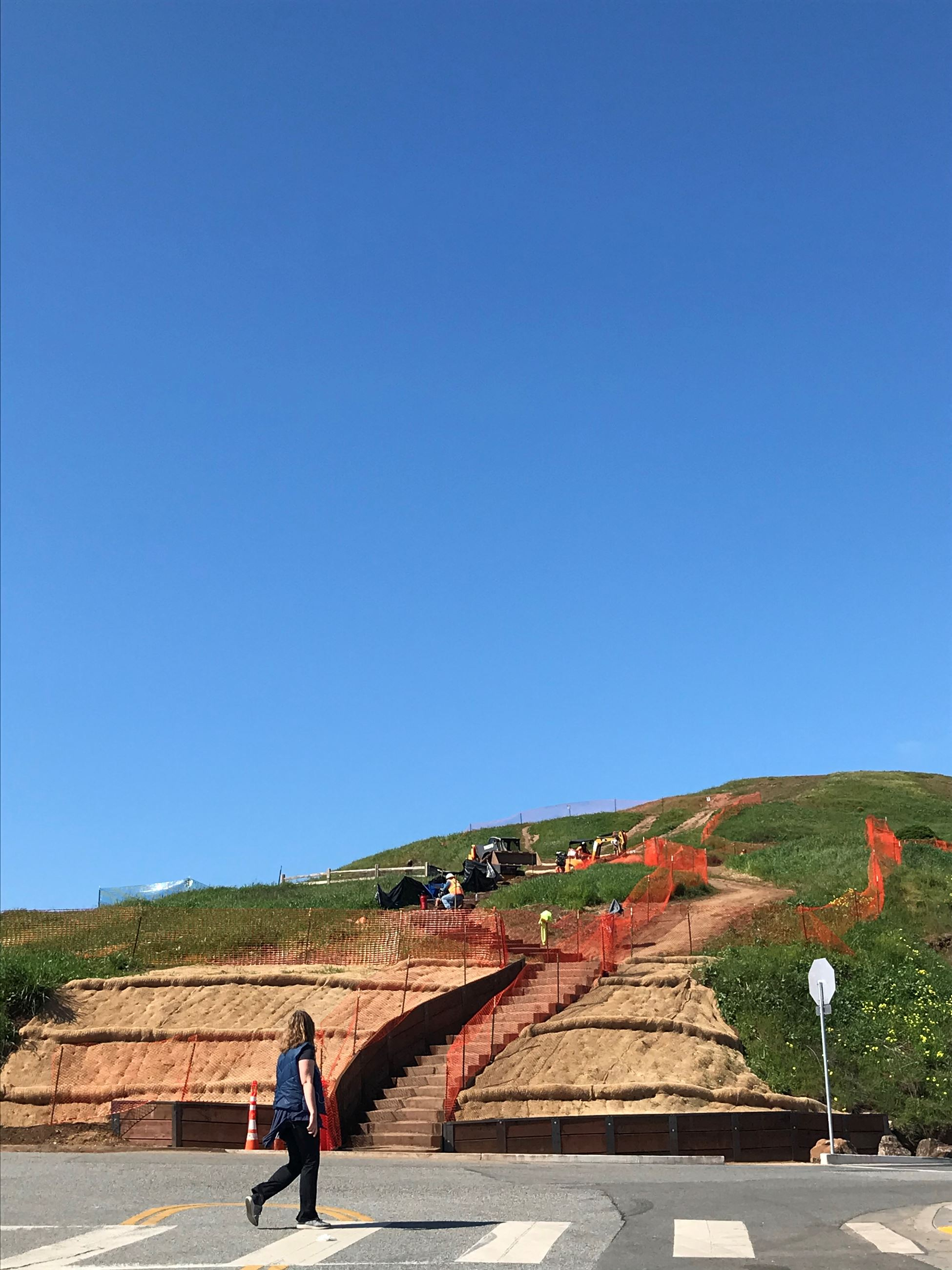 View of Box Steps Up Bernal Hill in construction with orange construction fencing, crosswalk (person