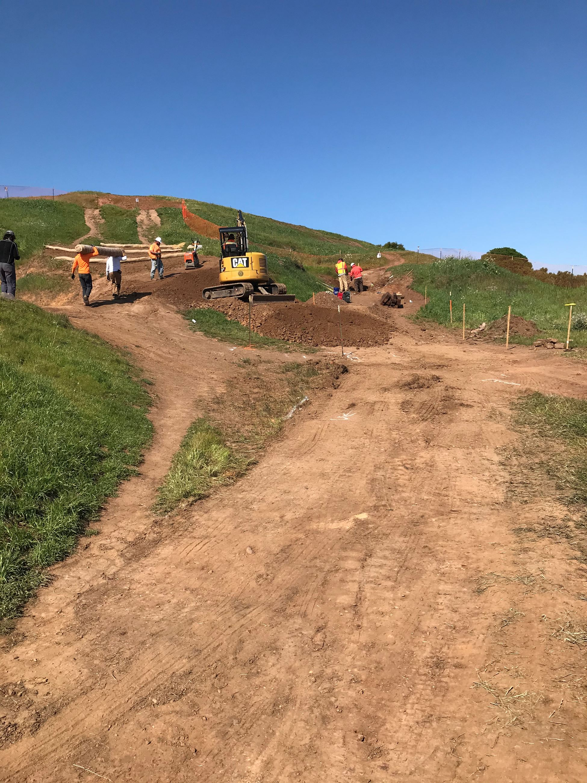 View of dirt trail at Bernal Heights with orange construction fencing and construction crew in the b