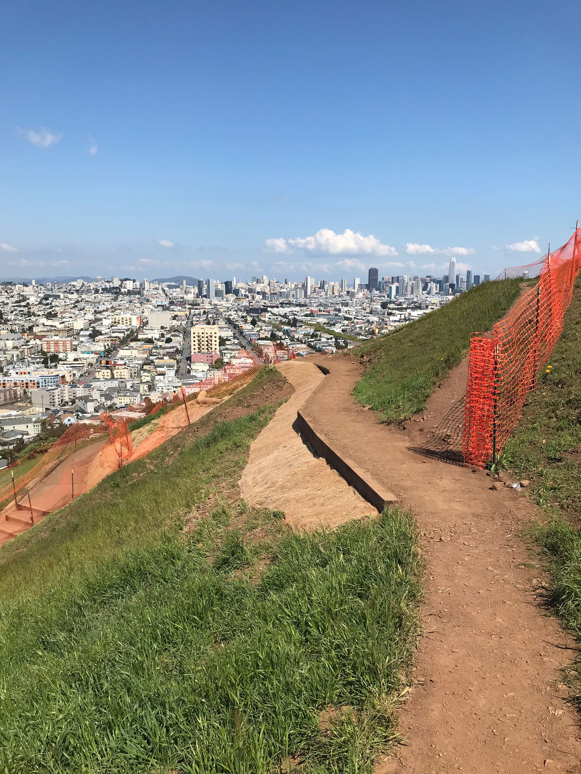 View of a trail splitting off three ways at Bernal Heights. Upper Trail is shown with orange constru