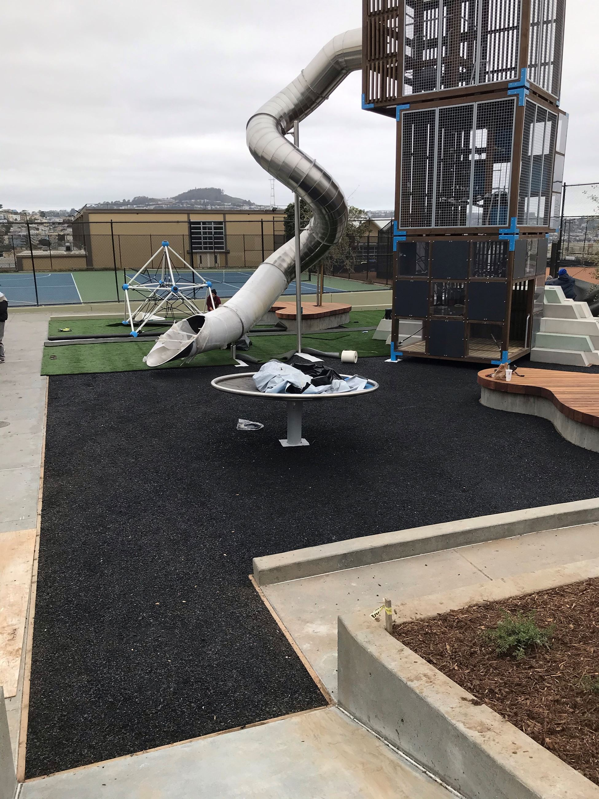 The image shows the newly poorede black rubber safety surfacing as well as the newly installed play