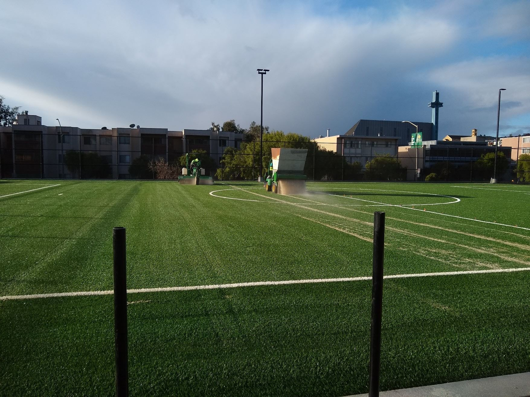 The image is of the small synthetic turf field receiving its natural infill with a machine spraying