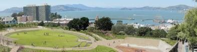 Image shows a future park, green grass, pathways and a view of the Bay in the background.