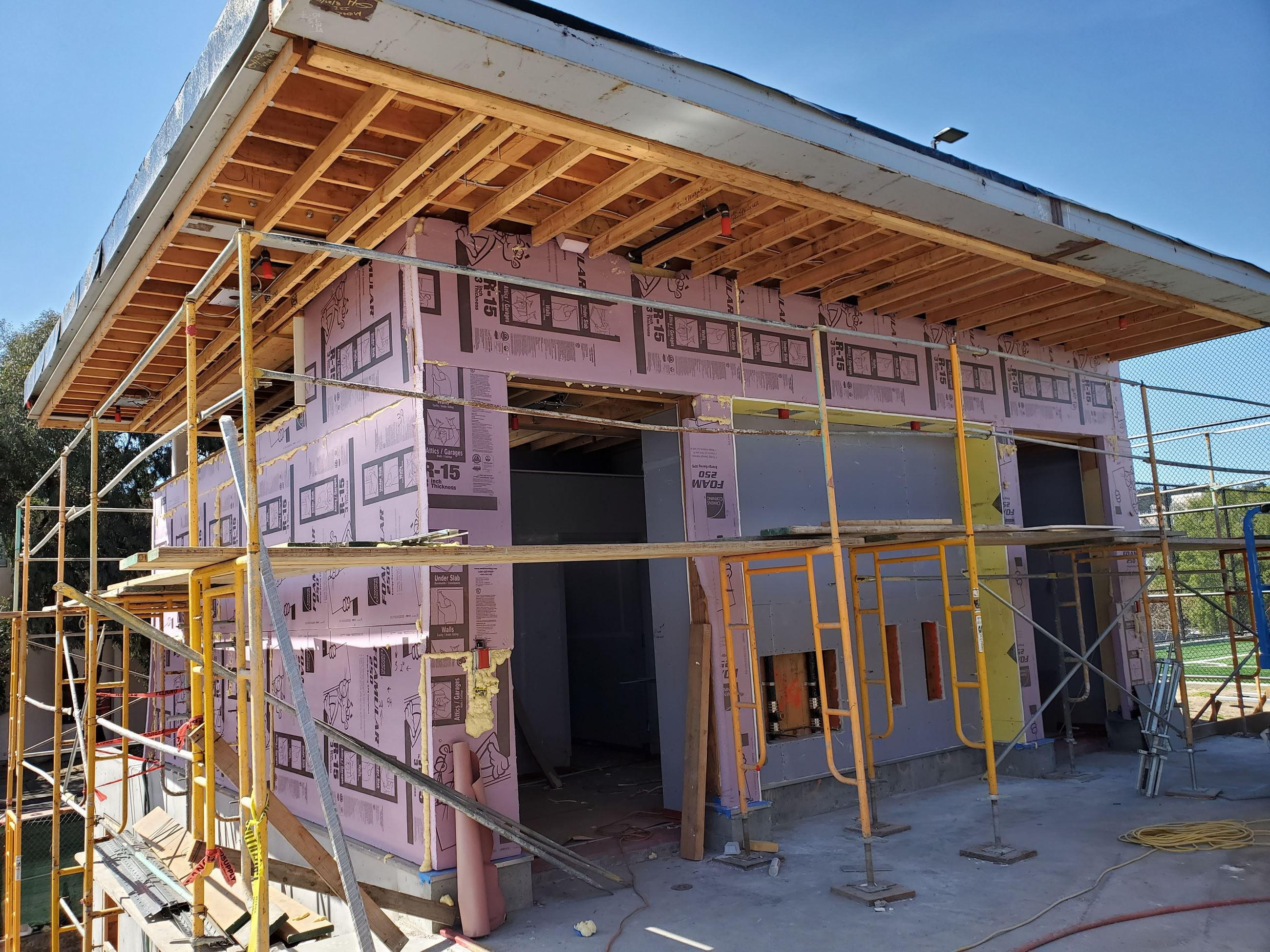 Photo is of the restroom being sealed with pink building wrap with scaffolding surrounding the struc
