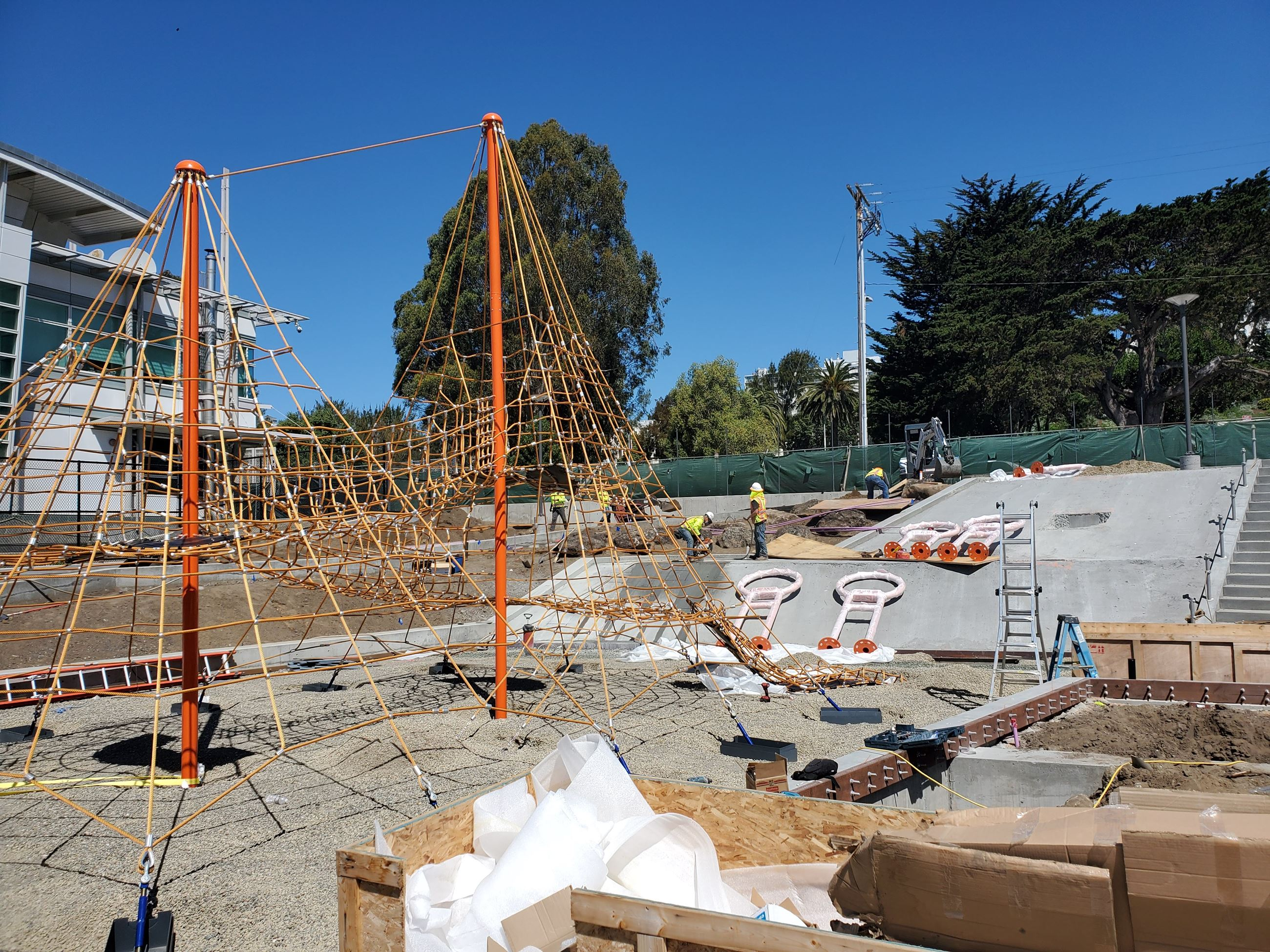 Margaret Hayward red playground structure being newly installed. The structure is centered on gravel