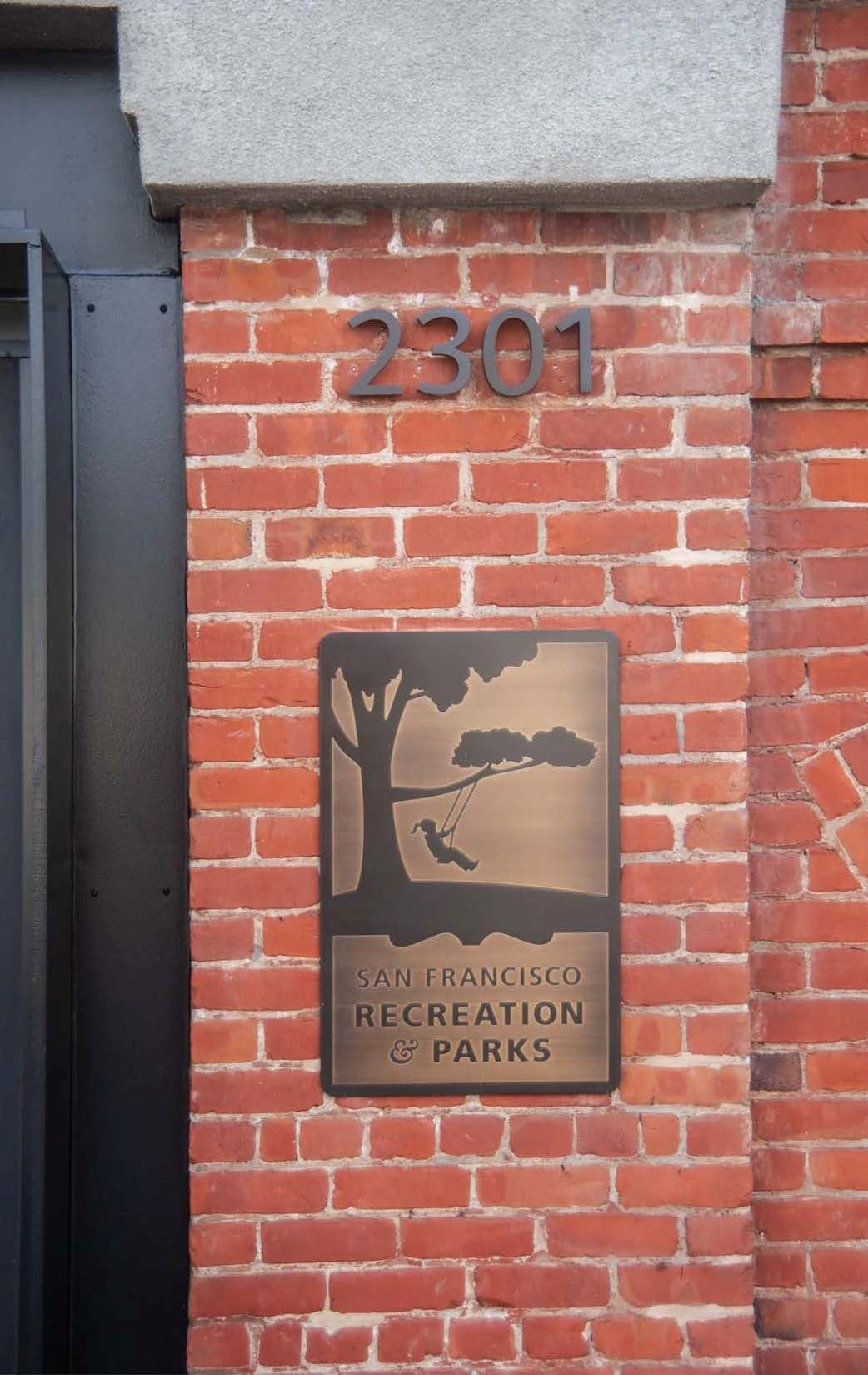 Image shows Geneva Car Barn Address number 2301 and bronze Rec and Park logo