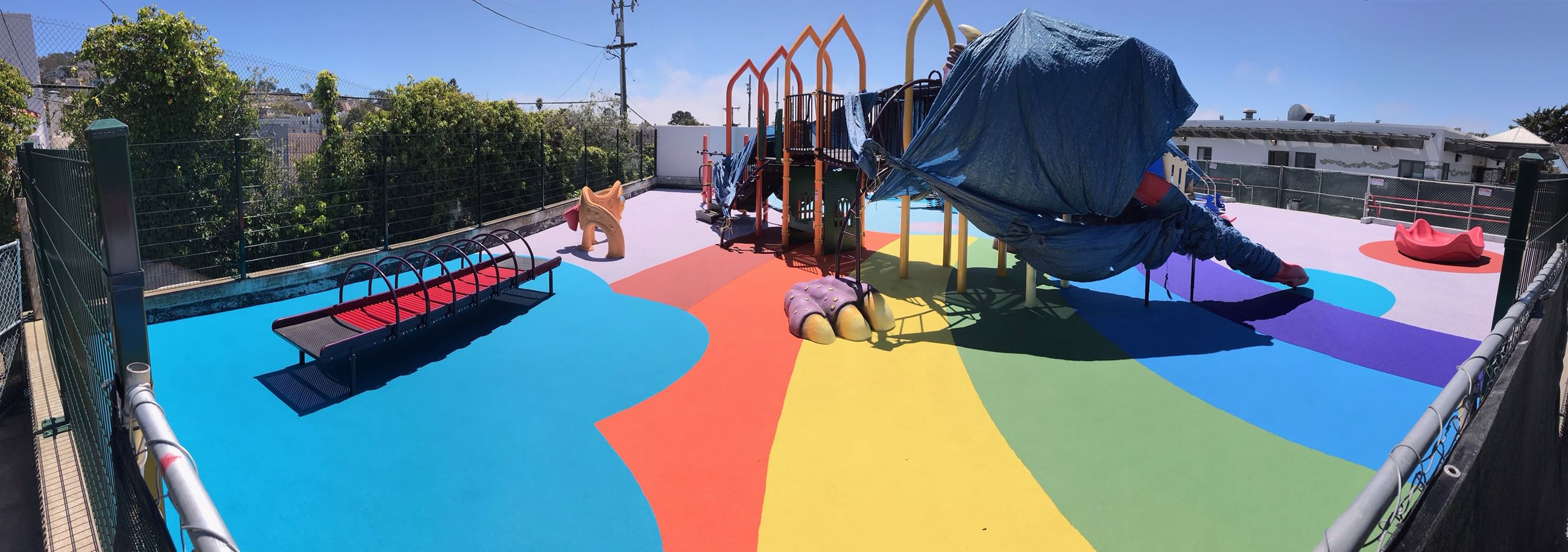 Image is of the West Portal Playground. The ground is covered in a poured in place rubber surfacing