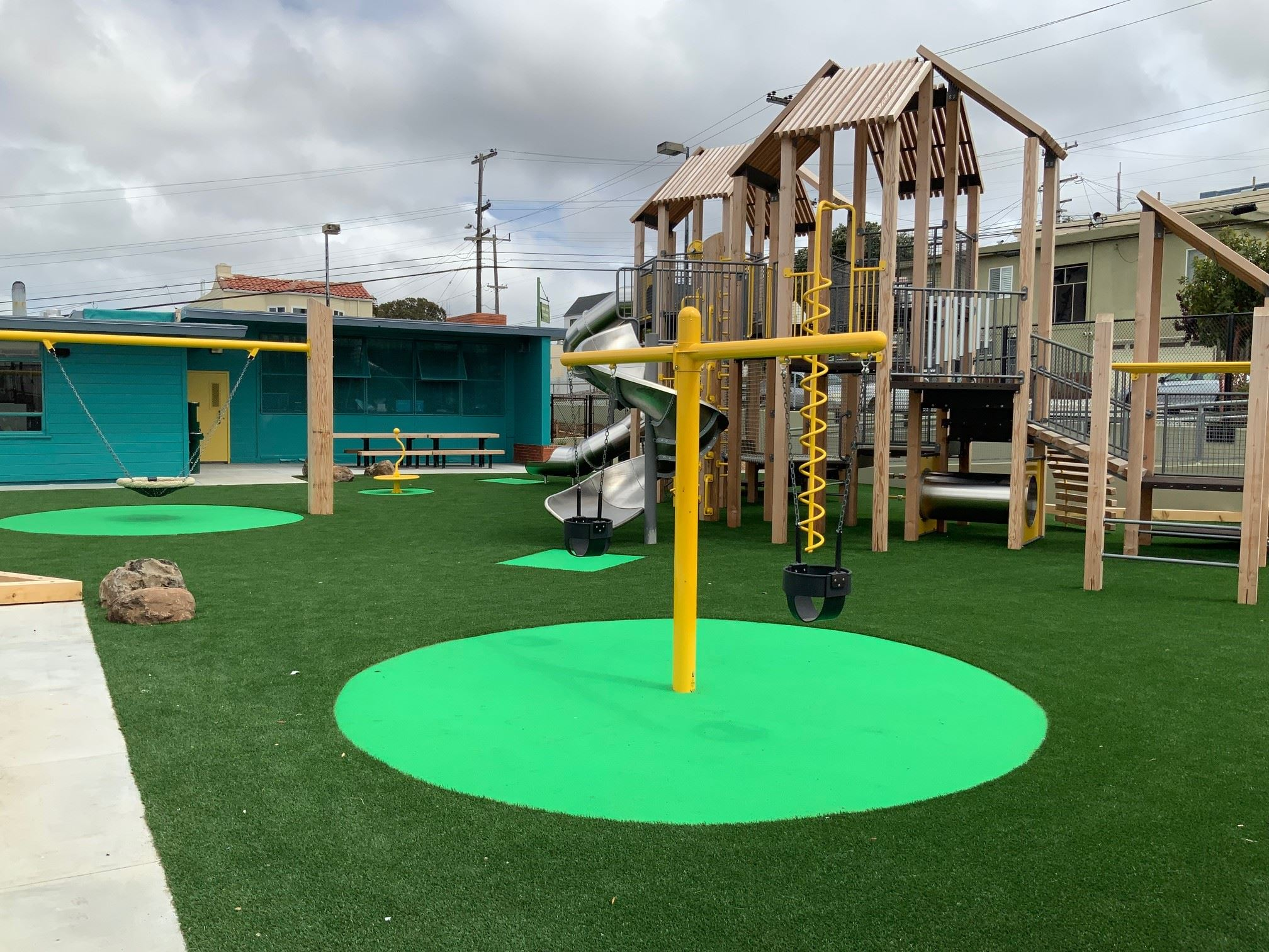 Merced Heights playground north view of the new play structure made out of wood, yellow metal tubing