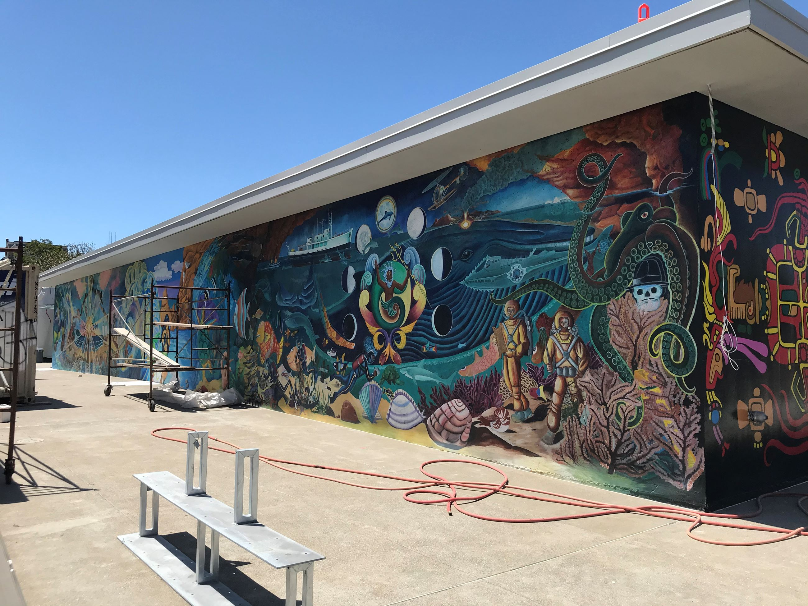 On the far left side of the mural is a green octopus underneath a red clay cliff, below is is two sc