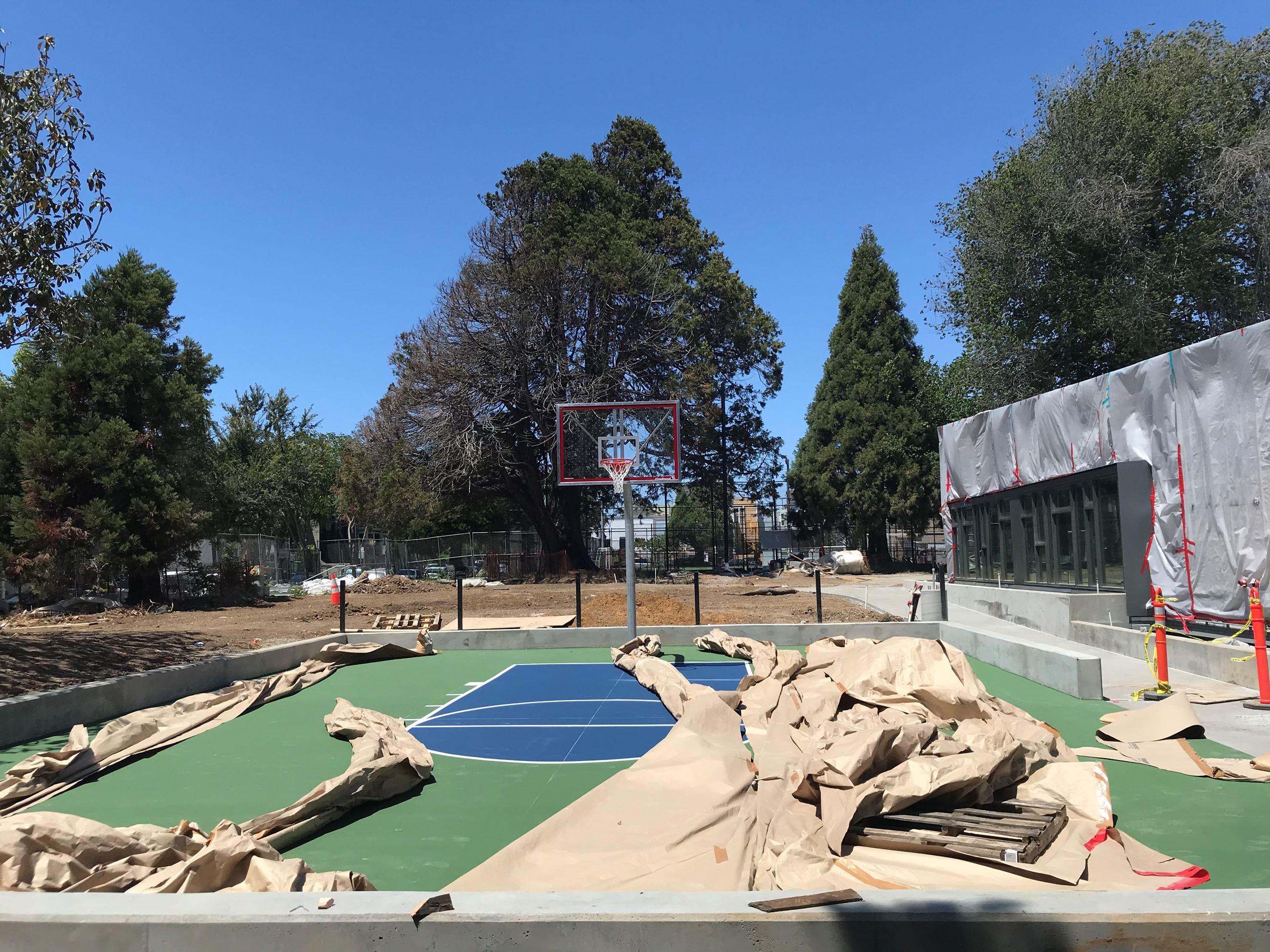 The photo shows a half basketball court in the middle, partially covered in brown construction paper