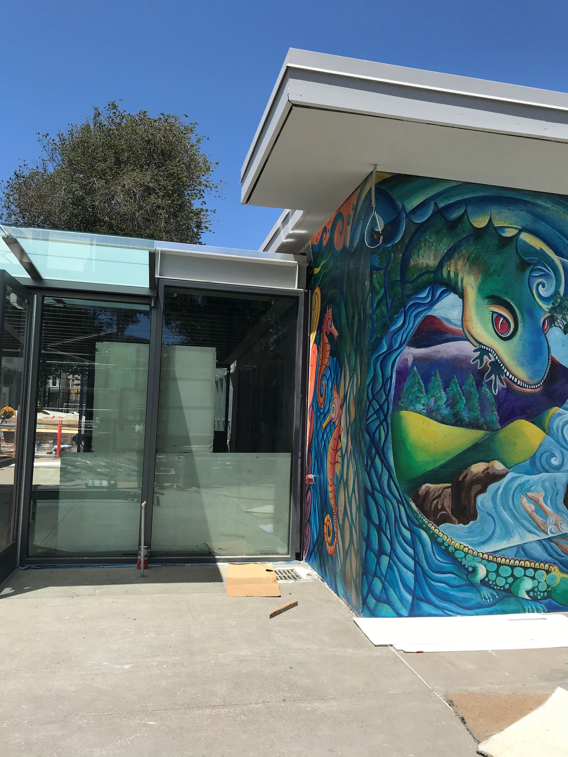 Mural with blue and green dragon is on the left. Window next to the entrance is shown on the right.