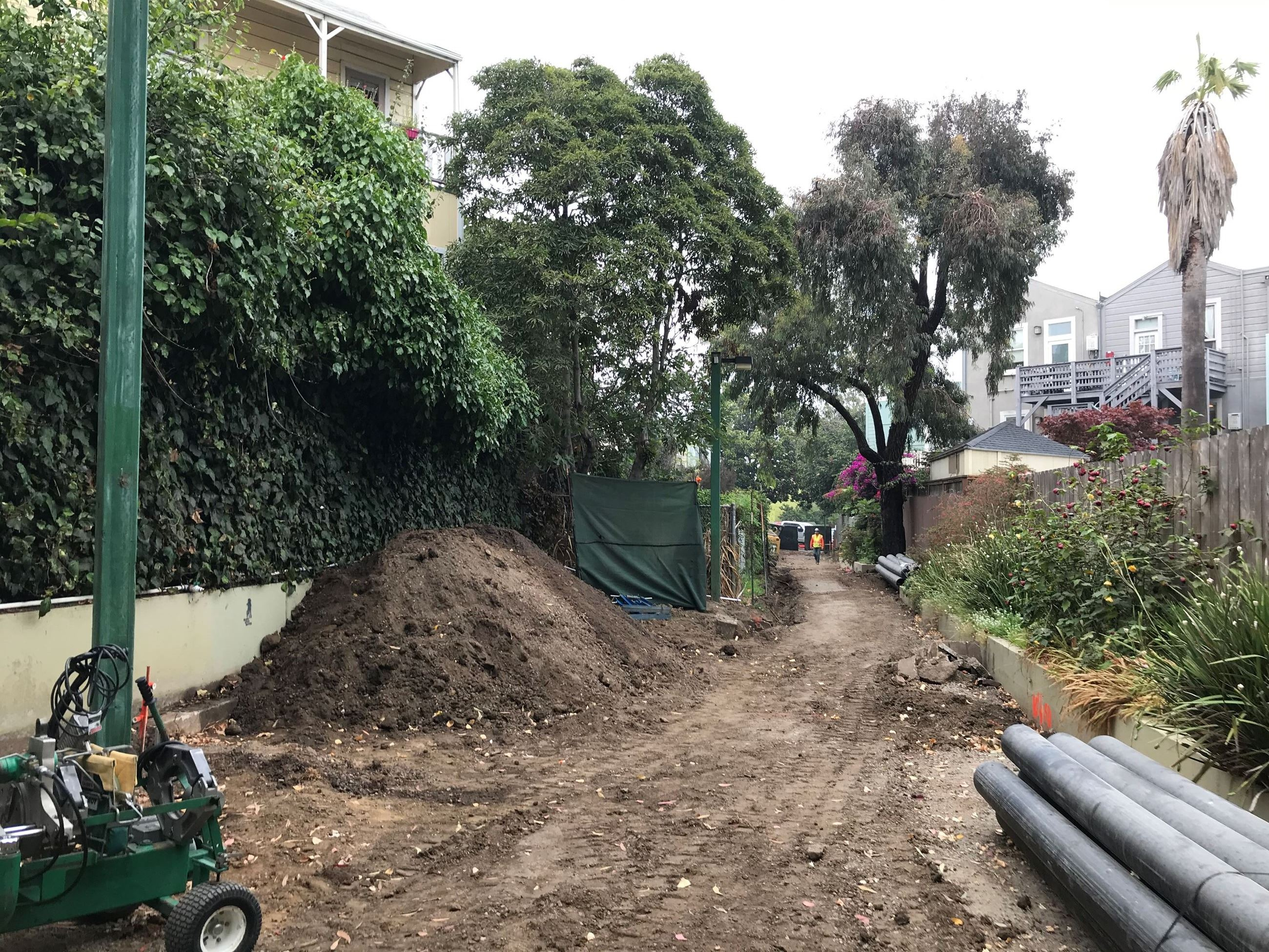 Large drainage pipes, light equipment and soil pile on top of fresh soil.