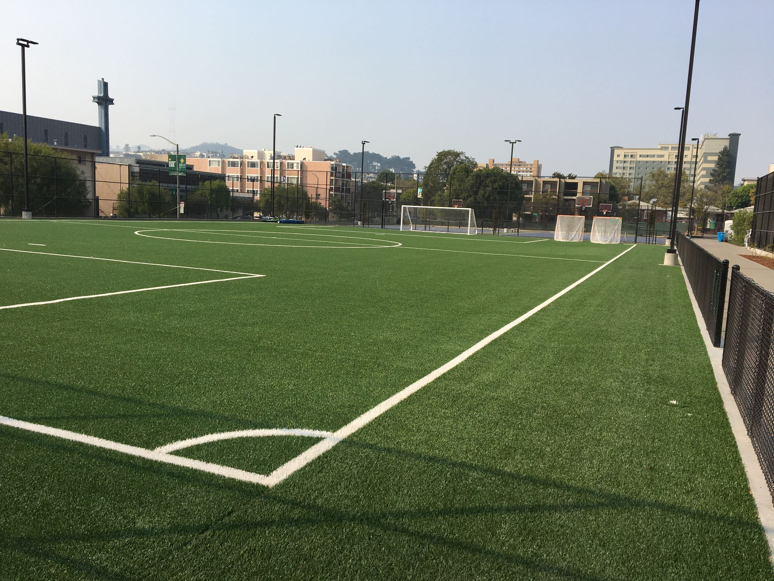 Multi purpose field with soccer goals surrounded by black coated metal fencing
