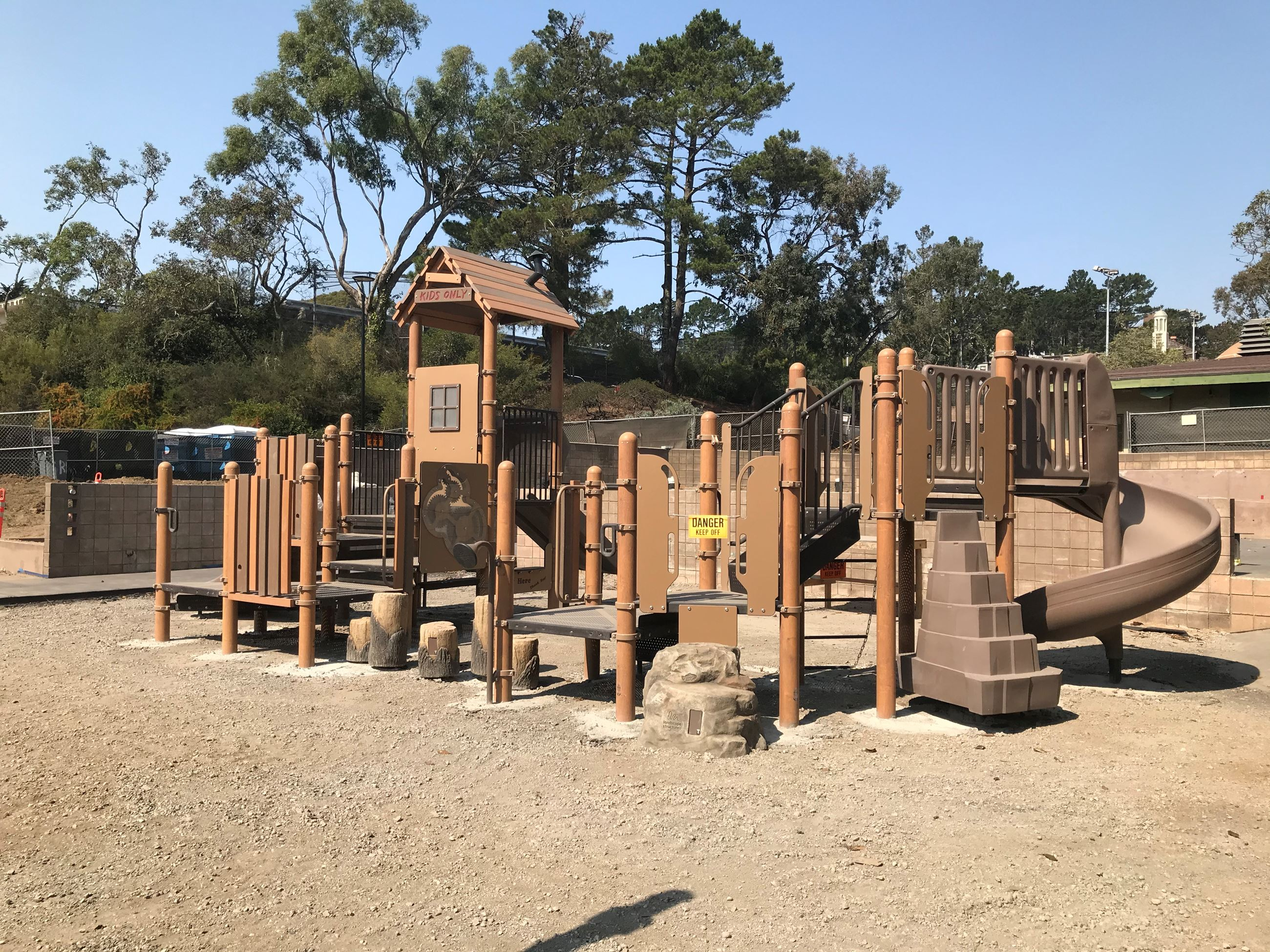 Play structure with brown climbing elements, rocks and boulders. Exposed soil.
