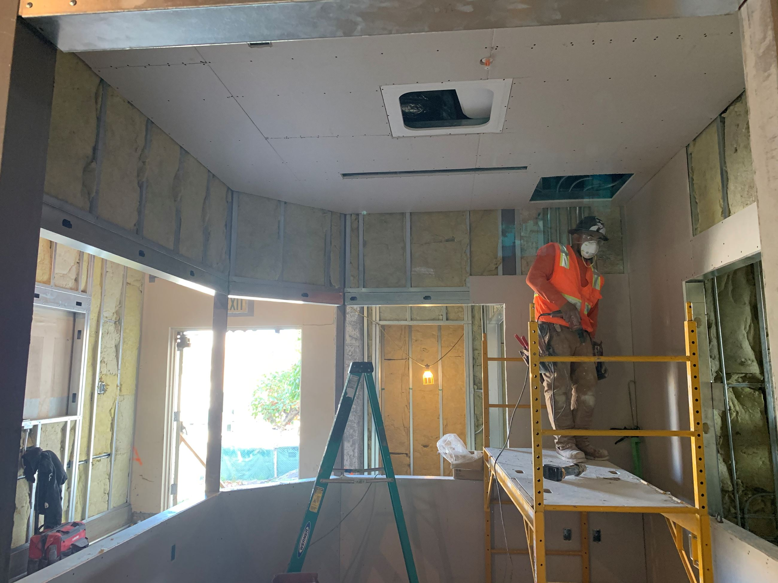 Construction worker installing drywall in front office of pool building.