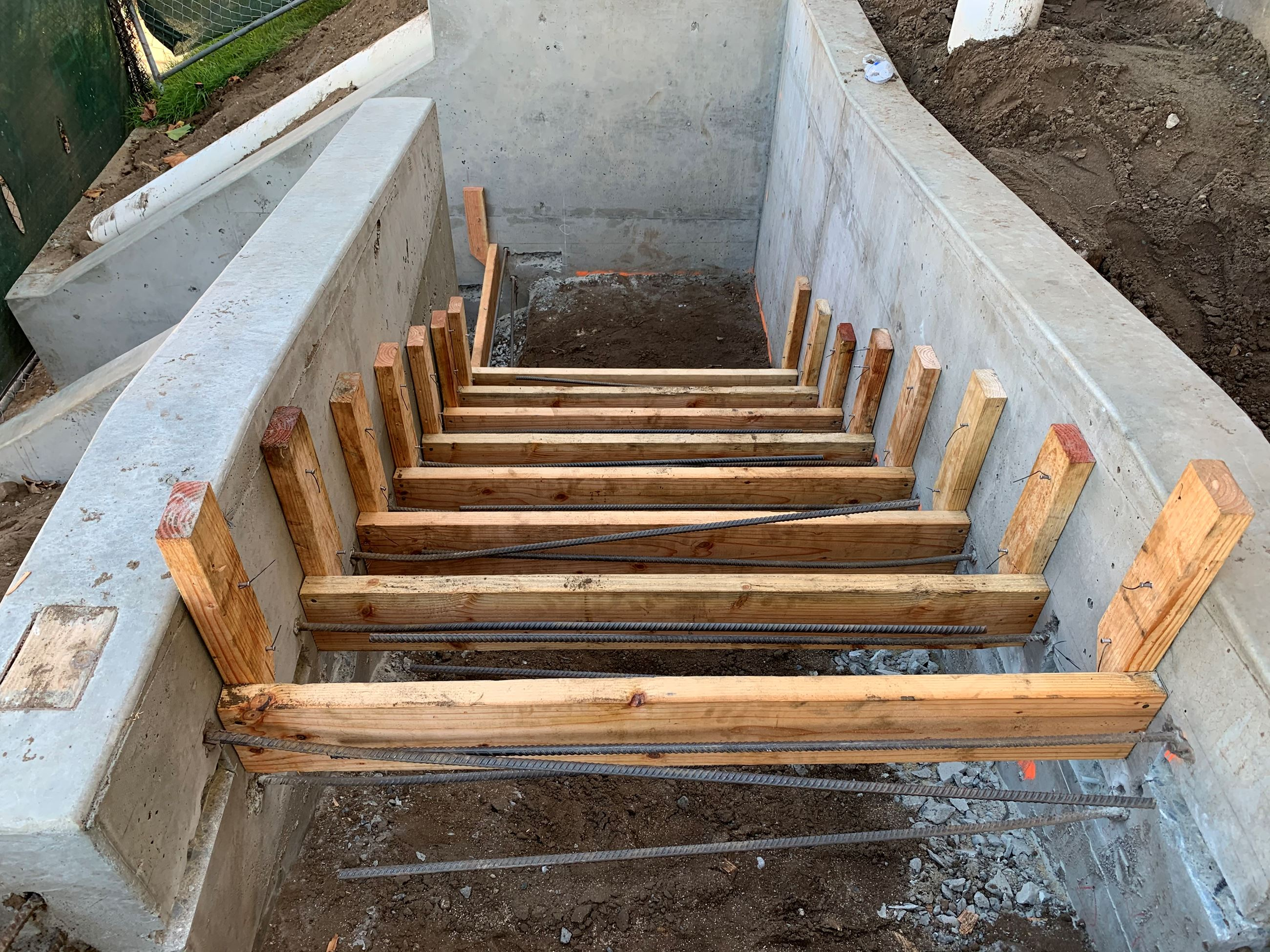Stair forms made of wood and rebar inside concrete walls.