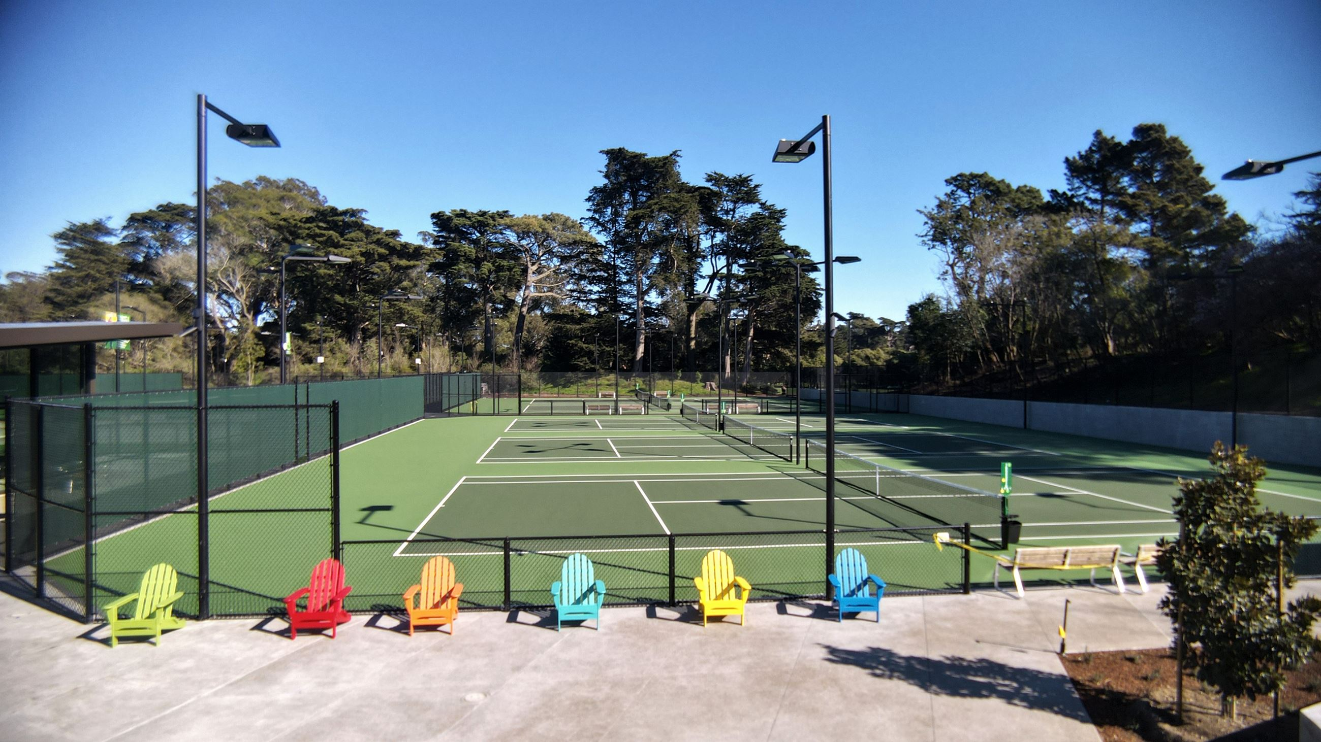 Adirondack chairs of multiple colors sit in front of the new tennis court.
